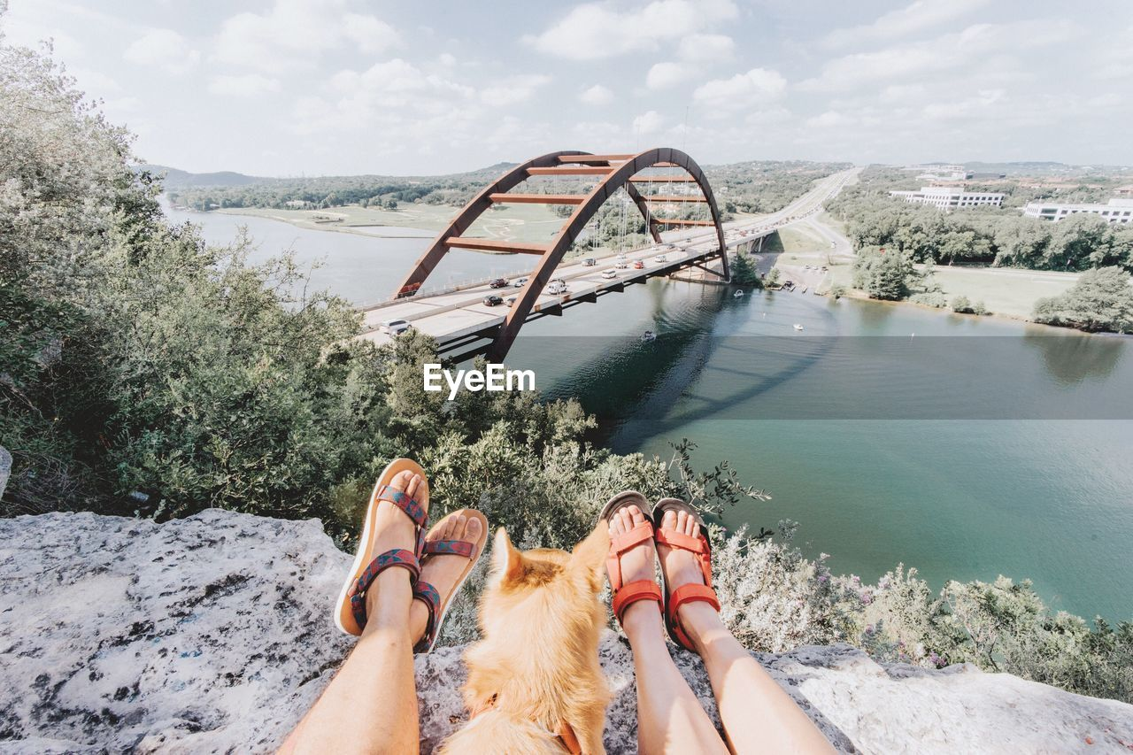 Low section of women with dog on mountain against river