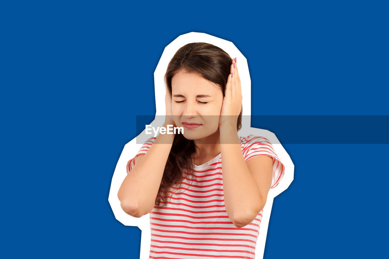 Young woman with hands covering ears standing against blue background
