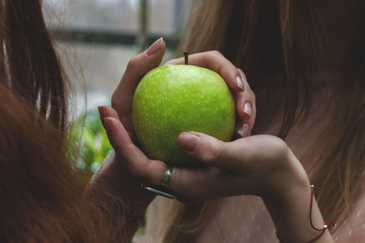 Close-Up Of Female Friends Holding Granny Smith Apple