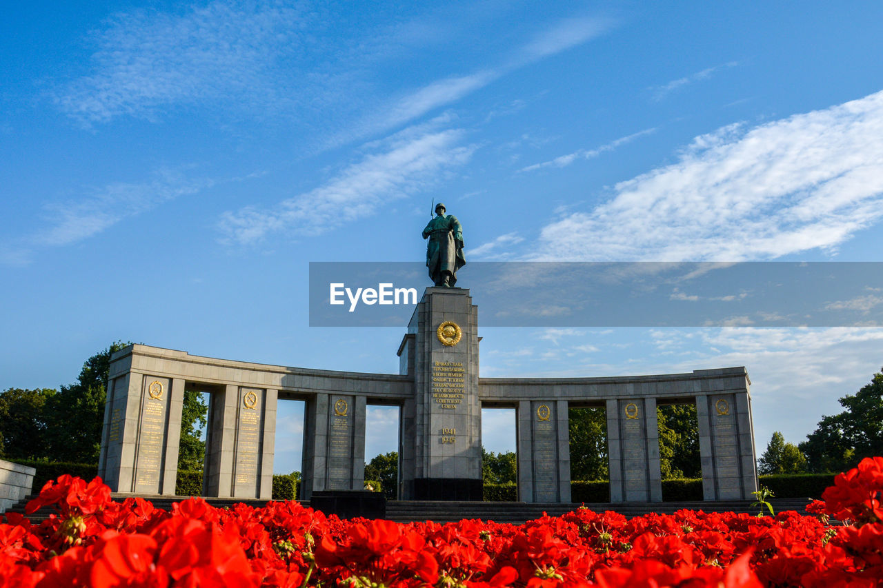 flower, sky, day, outdoors, low angle view, statue, cloud - sky, built structure, nature, architecture, beauty in nature, no people, tree, building exterior
