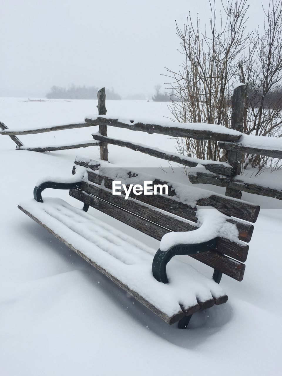 Snow Covered Bench On Field Against Sky
