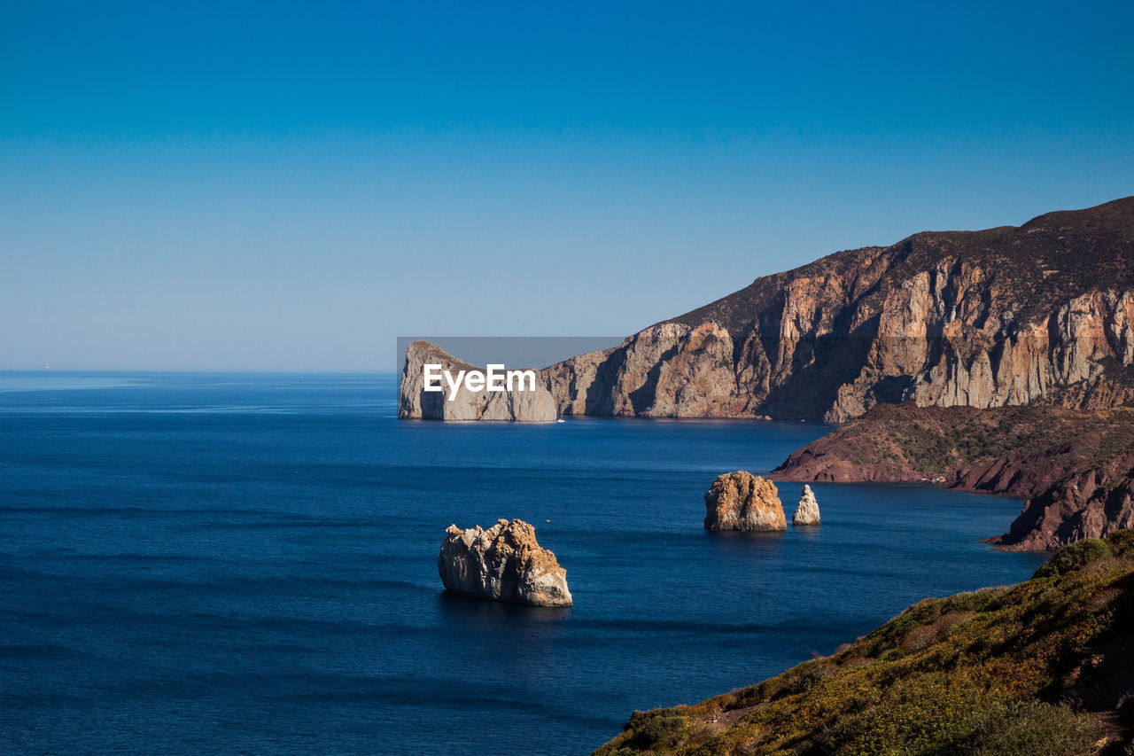 water, sky, sea, scenics - nature, beauty in nature, rock, tranquil scene, blue, tranquility, waterfront, nature, copy space, idyllic, rock - object, solid, no people, land, horizon, rock formation, horizon over water, outdoors, formation, stack rock