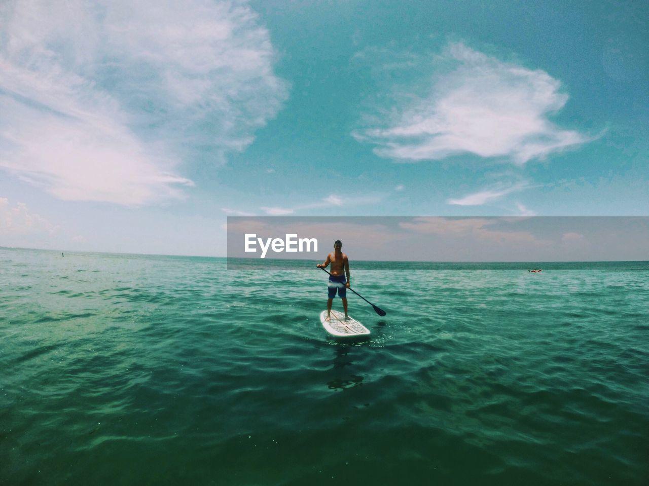 Man Paddleboarding Amidst Sea Against Sky