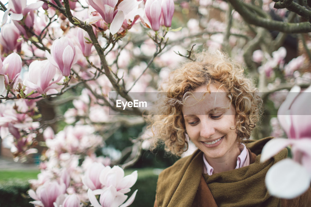 Smiling woman by flowers on branches