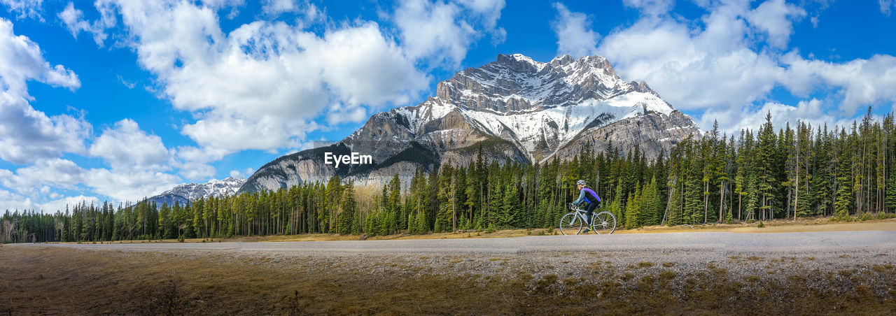 Side view of woman mountain biking by trees and mountain at banff national park