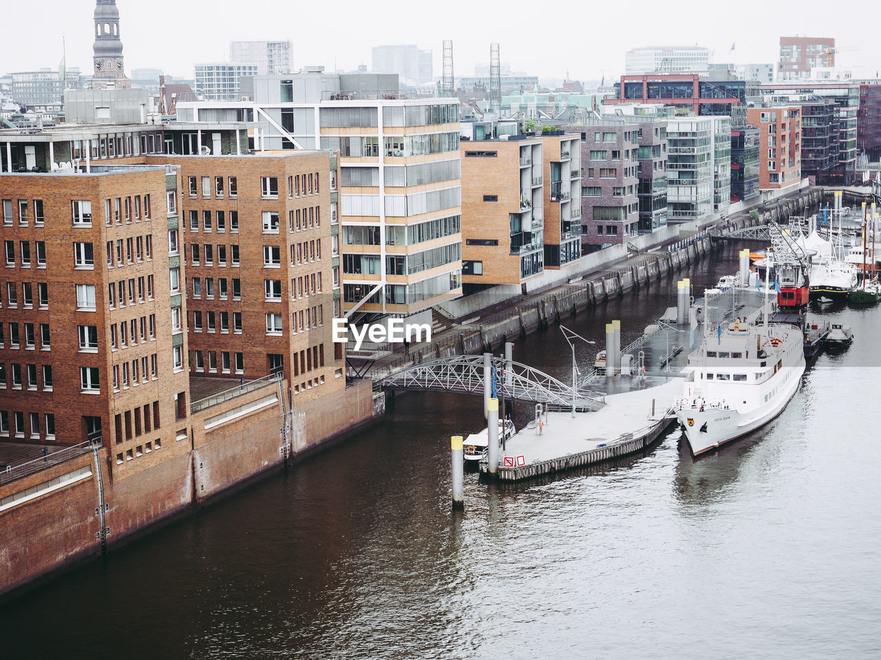 High Angle View Of Boats Moored On River By Buildings In City Against Sky