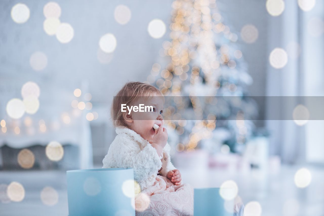 Little girl sorting new year gifts under the christmas tree