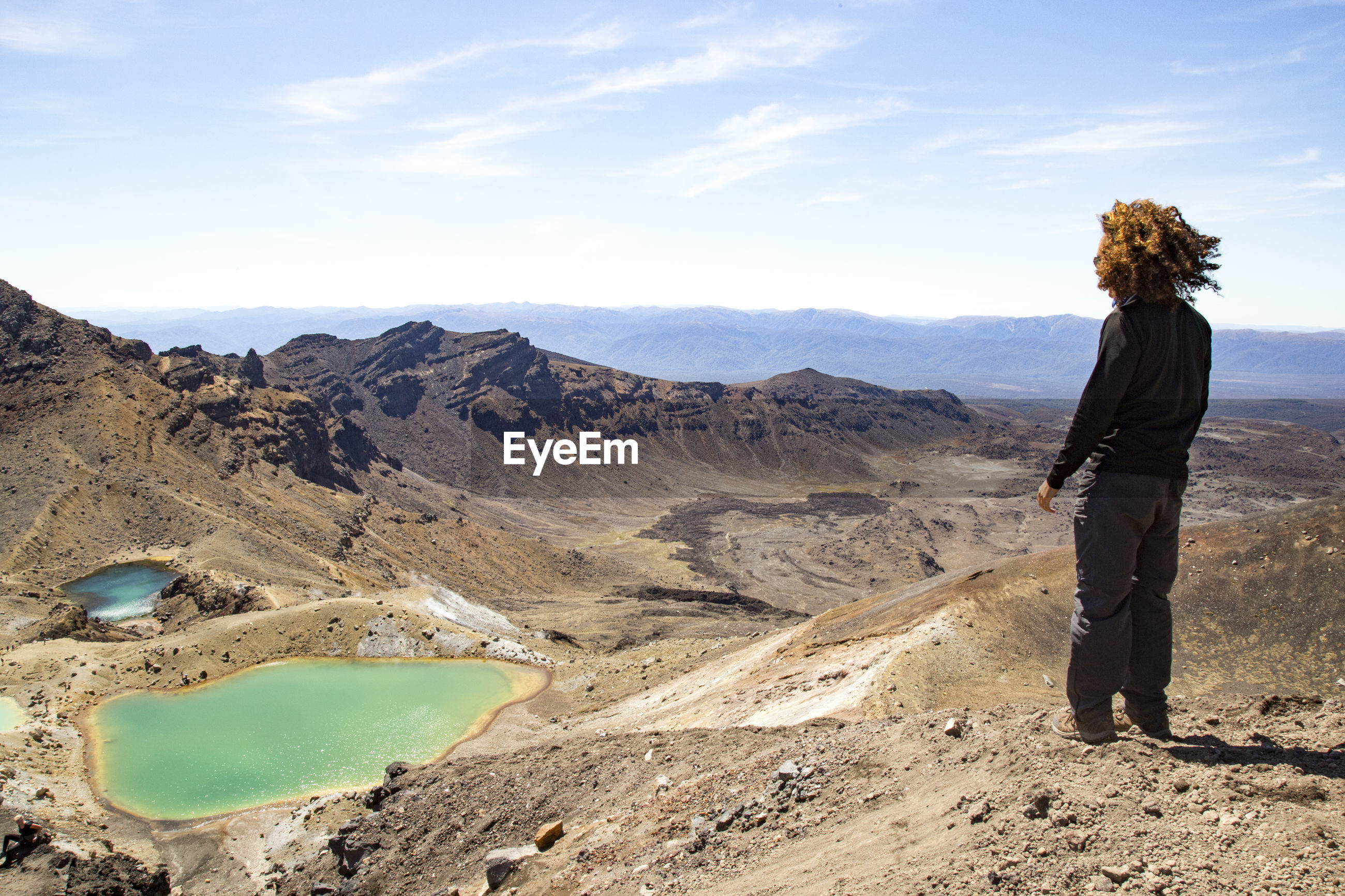 MAN STANDING ON MOUNTAIN LOOKING AT MOUNTAINS