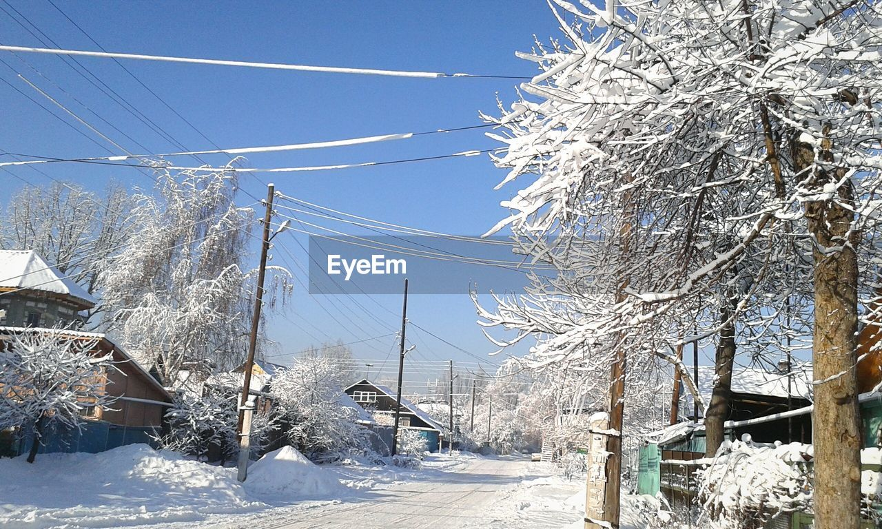 winter, snow, cold temperature, cable, tree, nature, white color, weather, day, outdoors, power line, sunlight, no people, beauty in nature, tranquility, blue, transportation, landscape, electricity pylon, bare tree, electricity, sky, scenics, built structure, clear sky, architecture, building exterior, ski lift