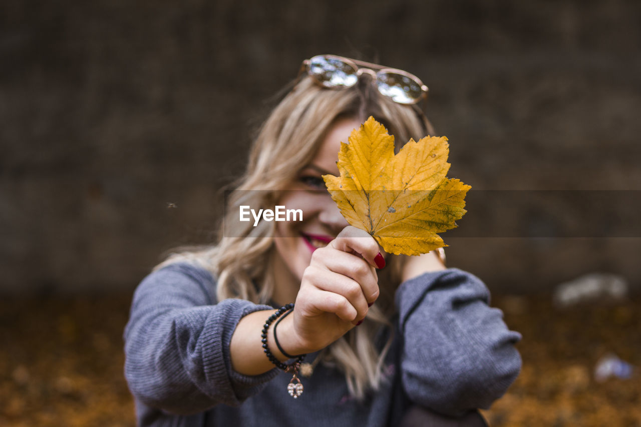 Portrait of woman showing maple leaf