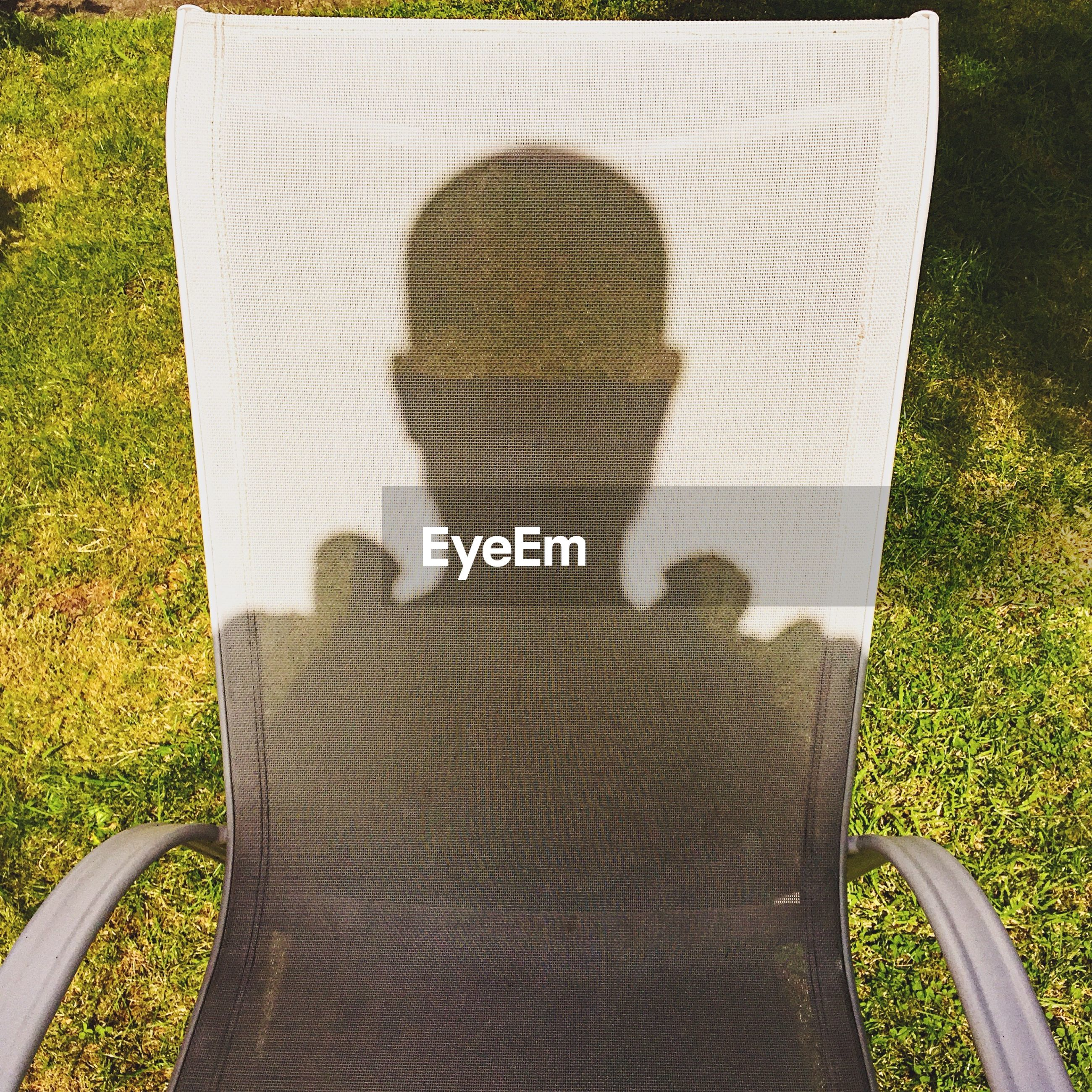 Shadow of person on chair at field