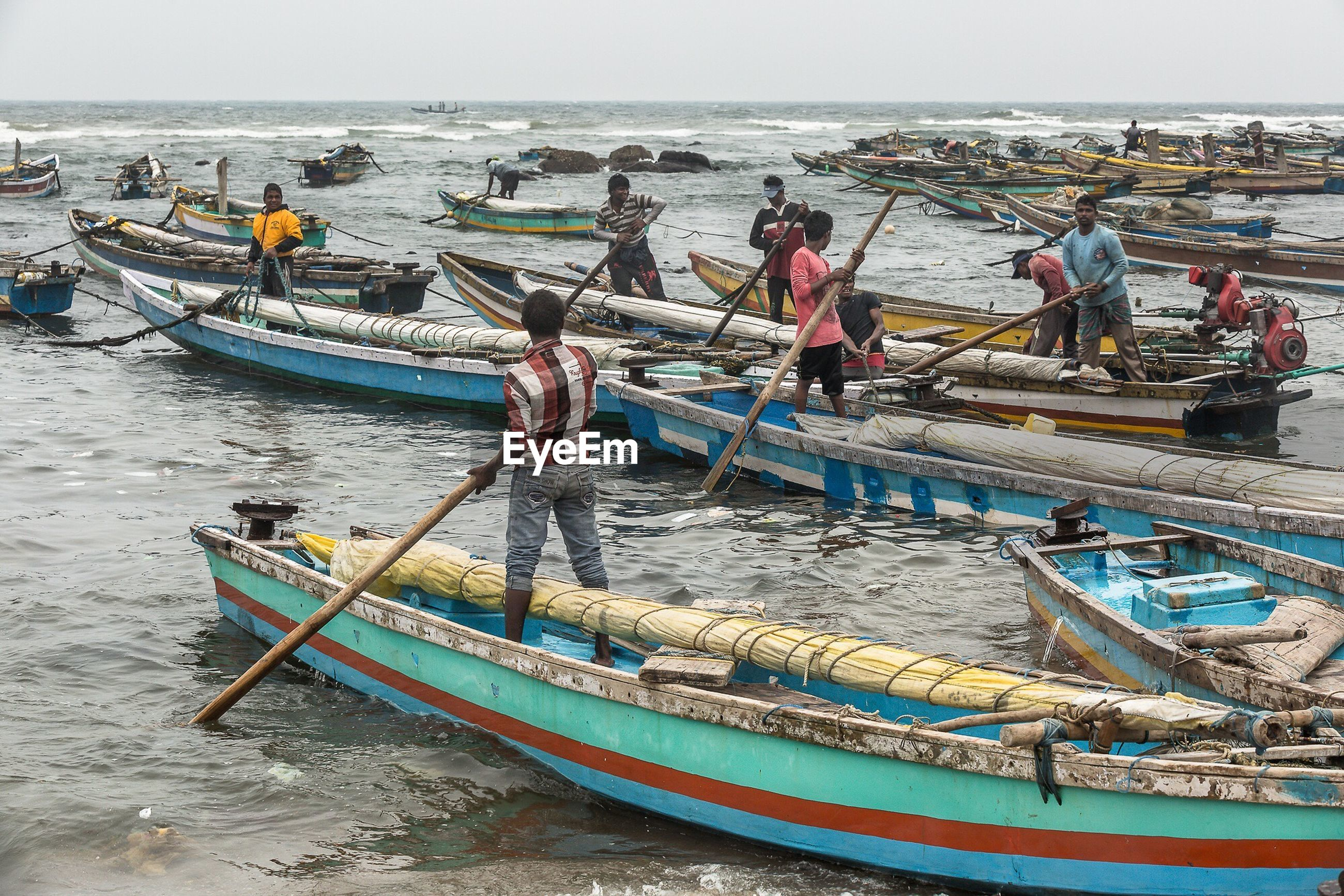 View of fisherman in boats against clear sky