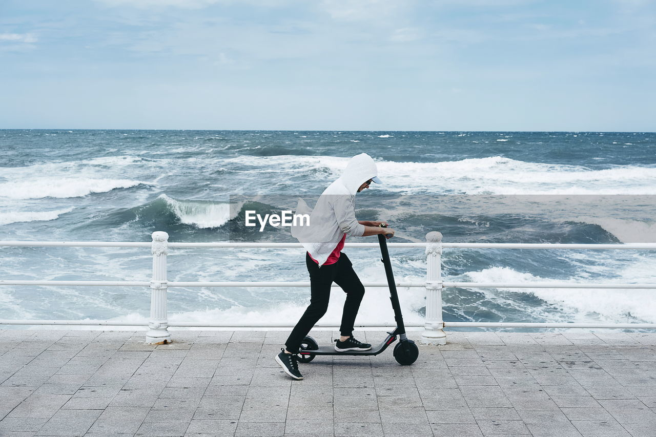 Man riding push scooter at beach against sky