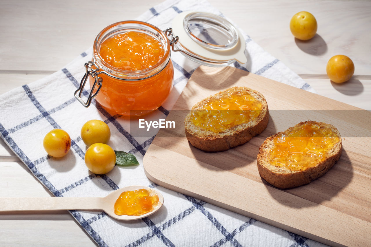 food and drink, food, freshness, jar, container, table, indoors, healthy eating, cutting board, still life, high angle view, fruit, wellbeing, wood - material, no people, eating utensil, bread, kitchen utensil, household equipment, spoon, breakfast, table knife