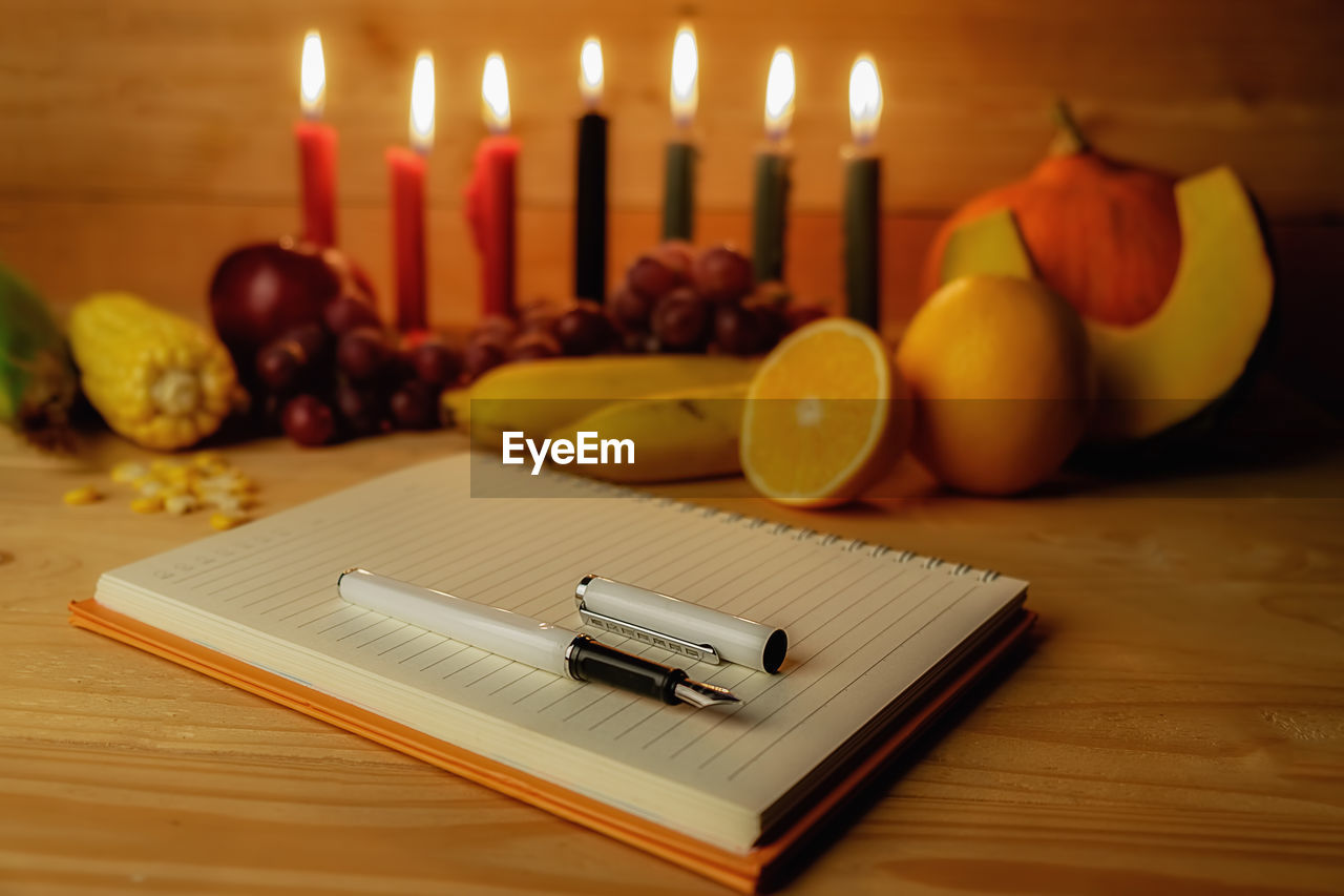 Close-up of pen on book by lit candles and fruits over table