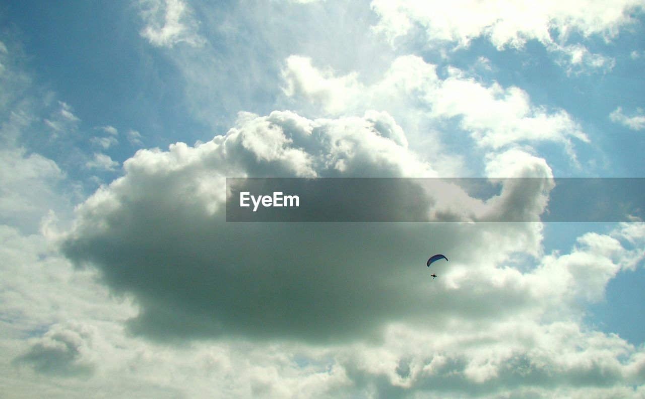 cloud - sky, sky, low angle view, adventure, extreme sports, mid-air, parachute, day, flying, paragliding, sport, nature, beauty in nature, leisure activity, freedom, unrecognizable person, transportation, outdoors, gliding, tranquility