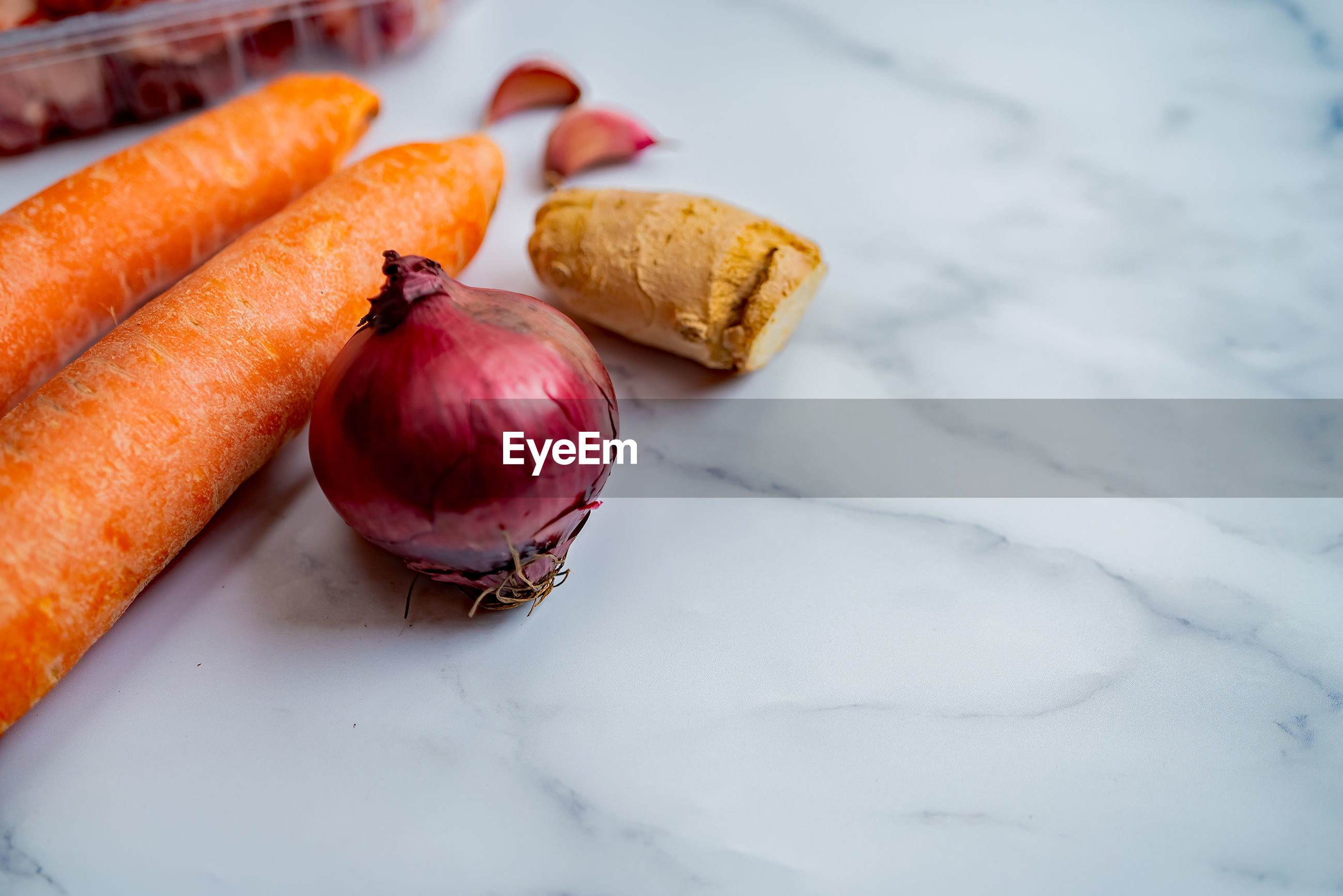 Selective focus of carrots on a white marble background