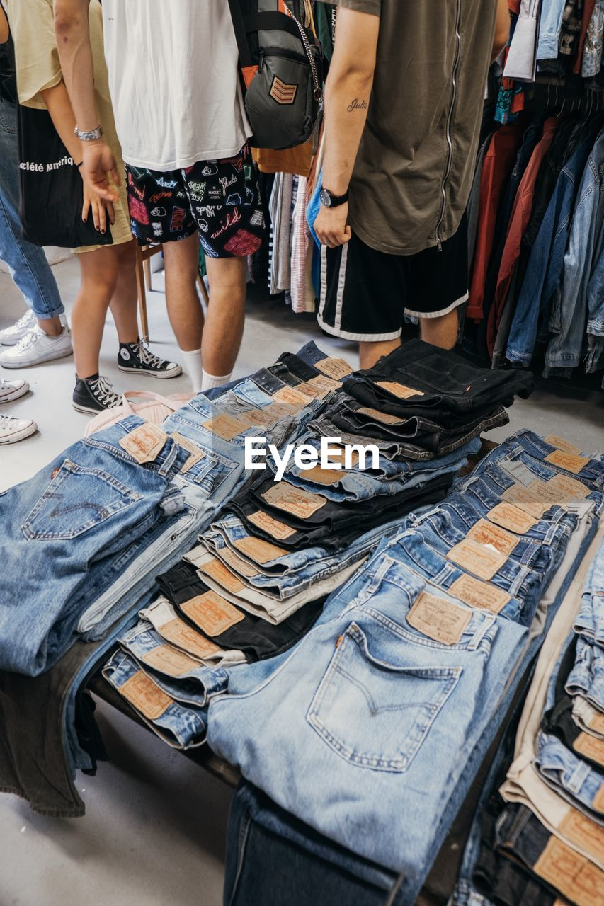 retail, shopping, casual clothing, textile, choice, real people, people, variation, standing, store, for sale, indoors, low section, market, large group of objects, arrangement, collection, clothing, side by side, lifestyles, retail display, jeans, consumerism, shorts