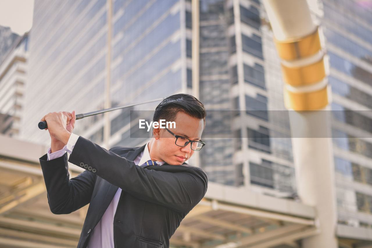 Young Businessman Swinging Golf Club Against Buildings In City