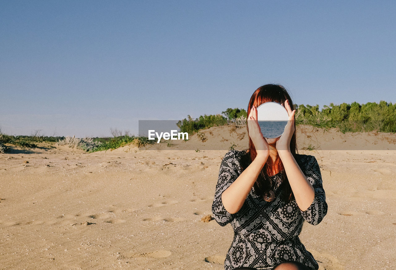 Woman Covering Face With Mirror At Sandy Beach Against Clear Sky