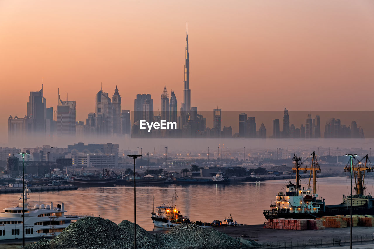 View Of Buildings In City At Sunset