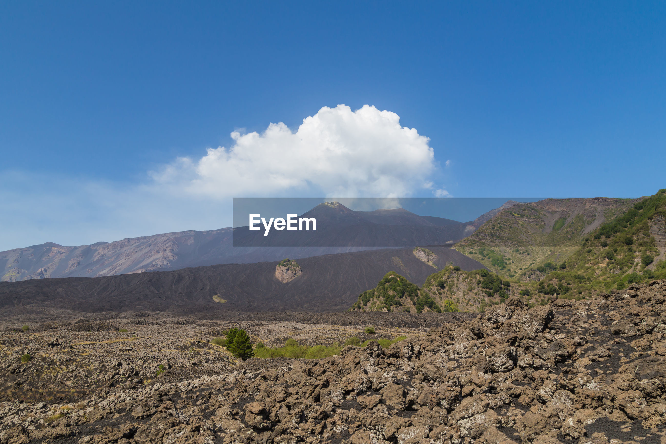Scenic landscape around active mt. etna volcano. steam clouds rising up from the crater.