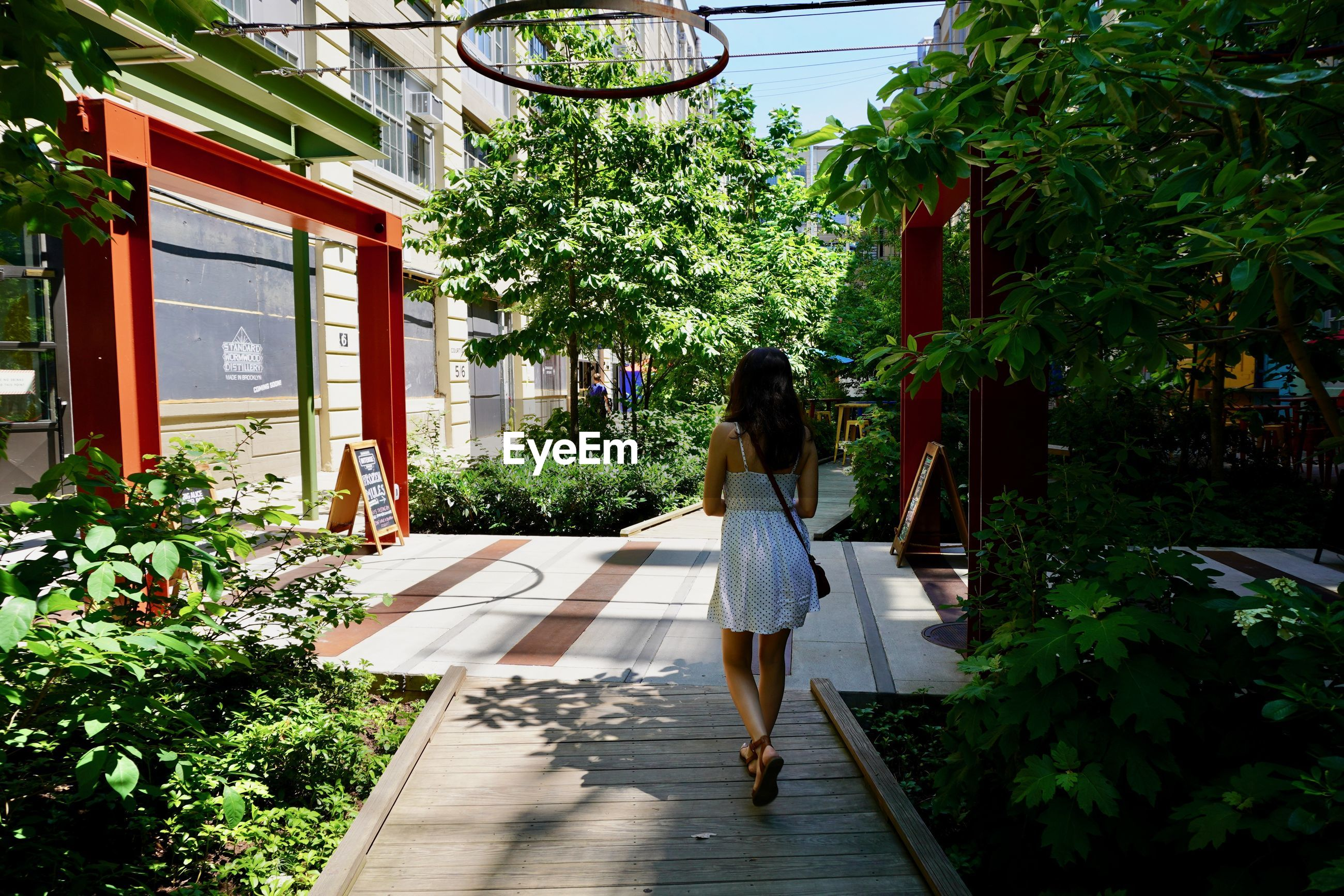 REAR VIEW OF WOMAN WALKING BY BUILDING AGAINST TREES