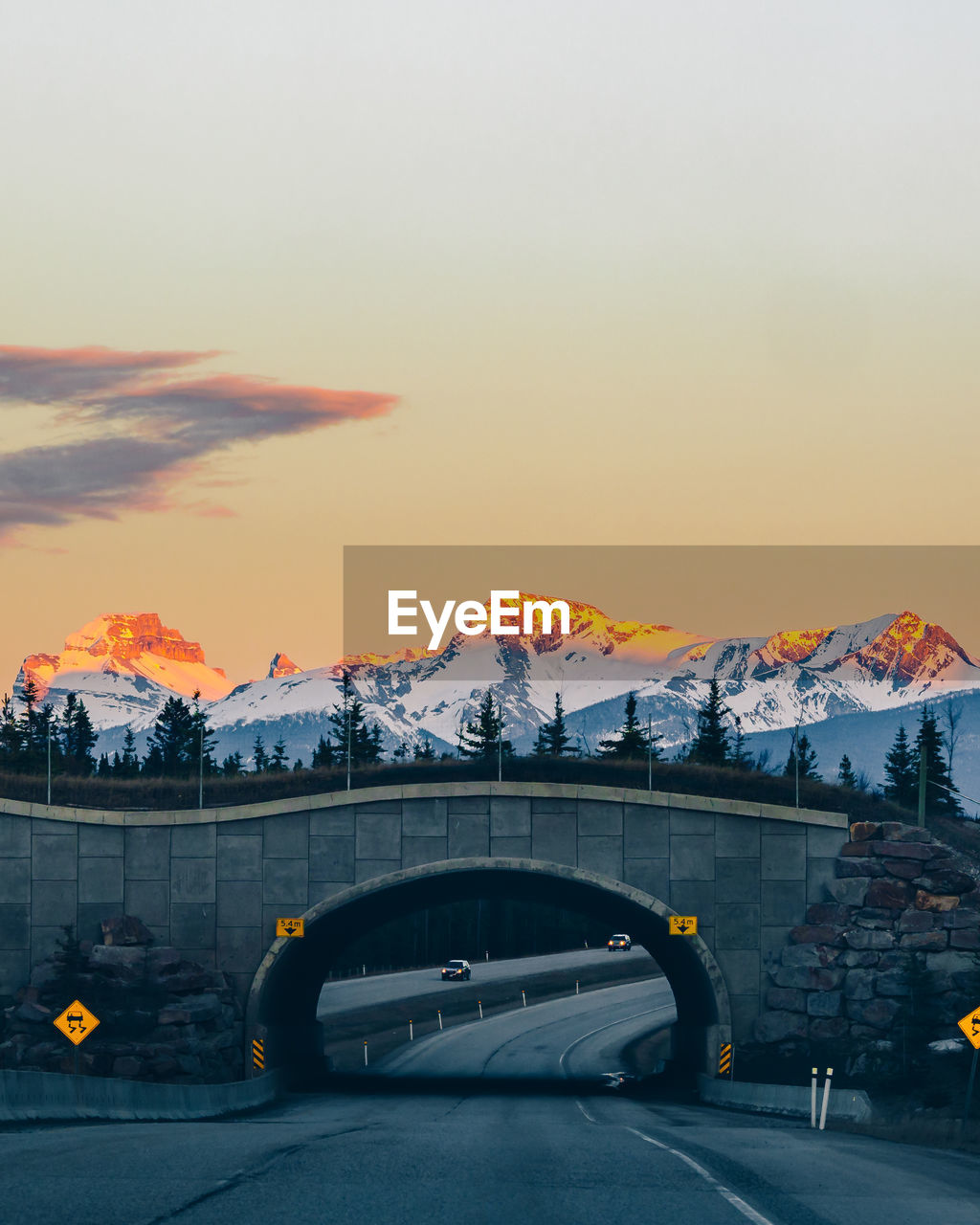 Arch Bridge And Snowcapped Mountains Against Sky During Sunset