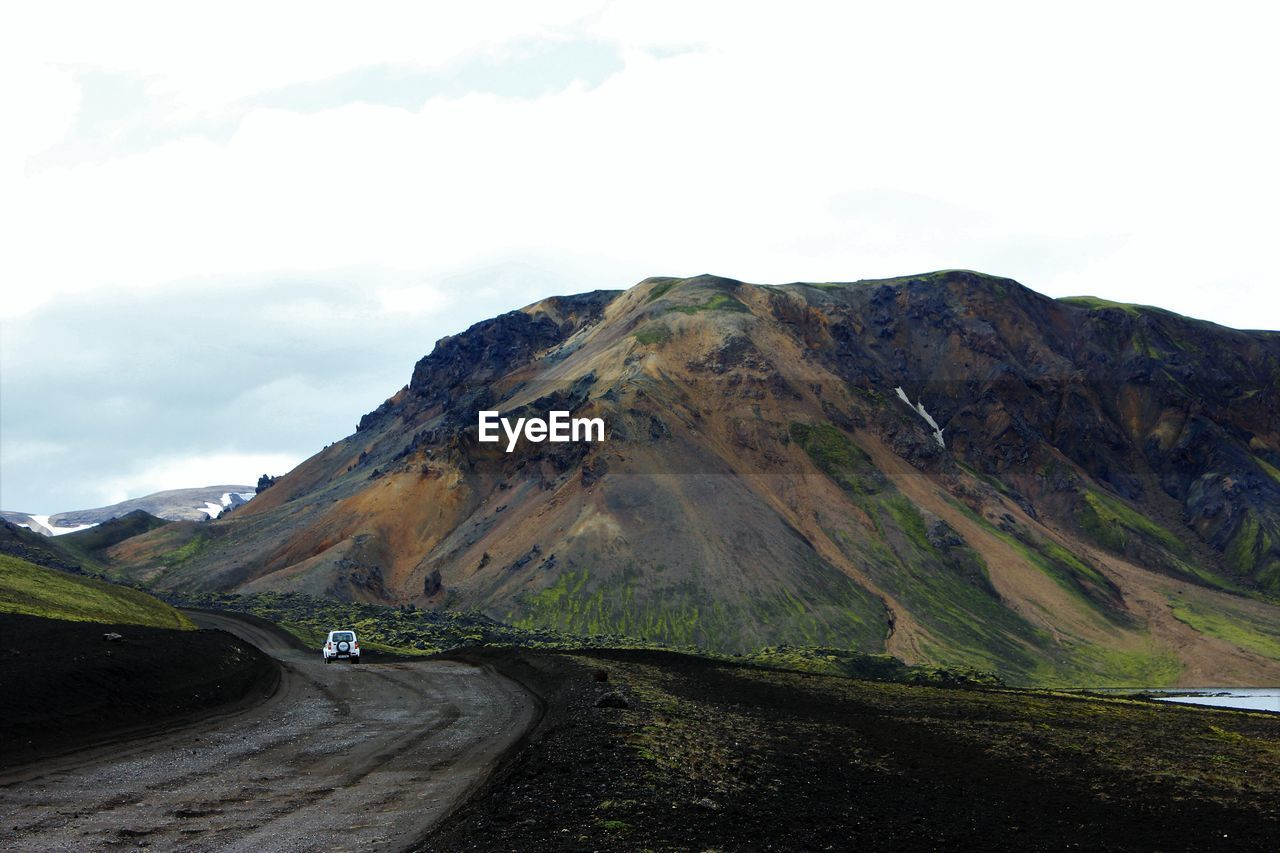 Road passing through mountains against sky