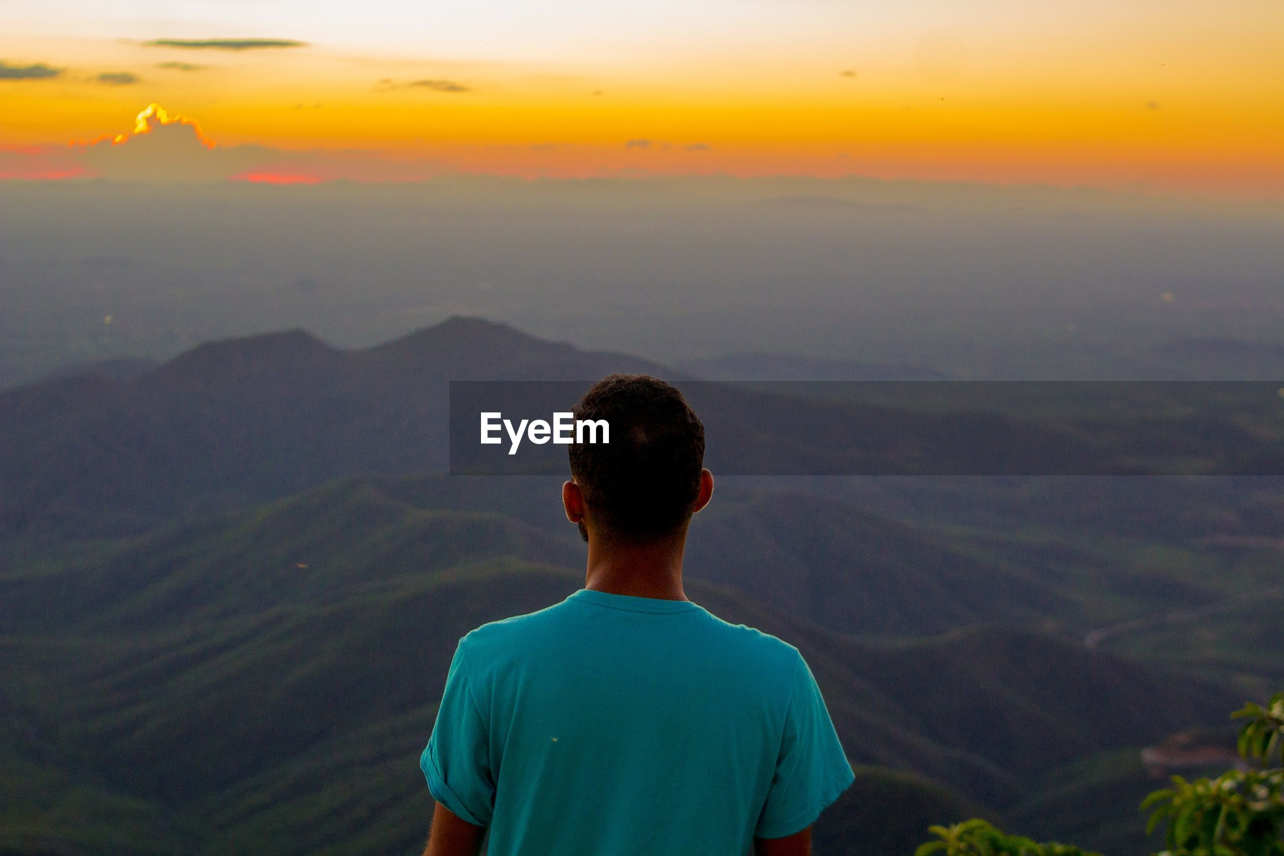 Rear view of man on landscape against sky at sunset