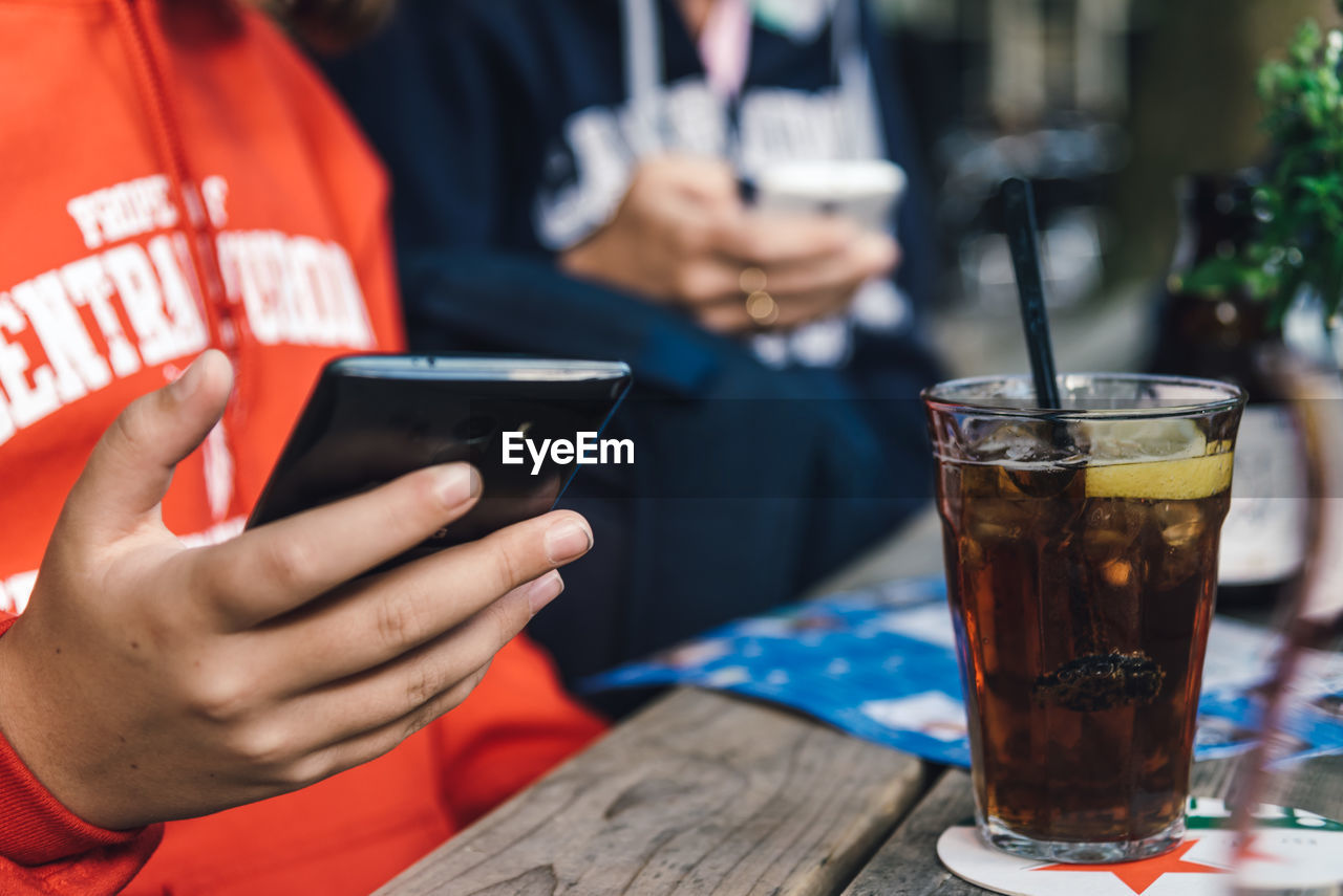 Midsection Of Woman Text Messaging On Phone While Sitting At Table