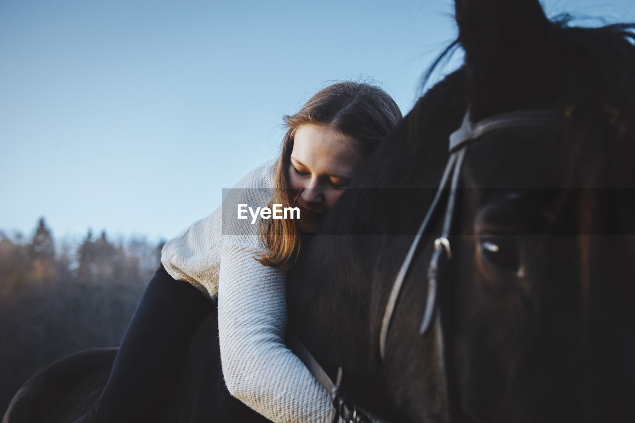 Close-Up Of Woman Hugging Horse
