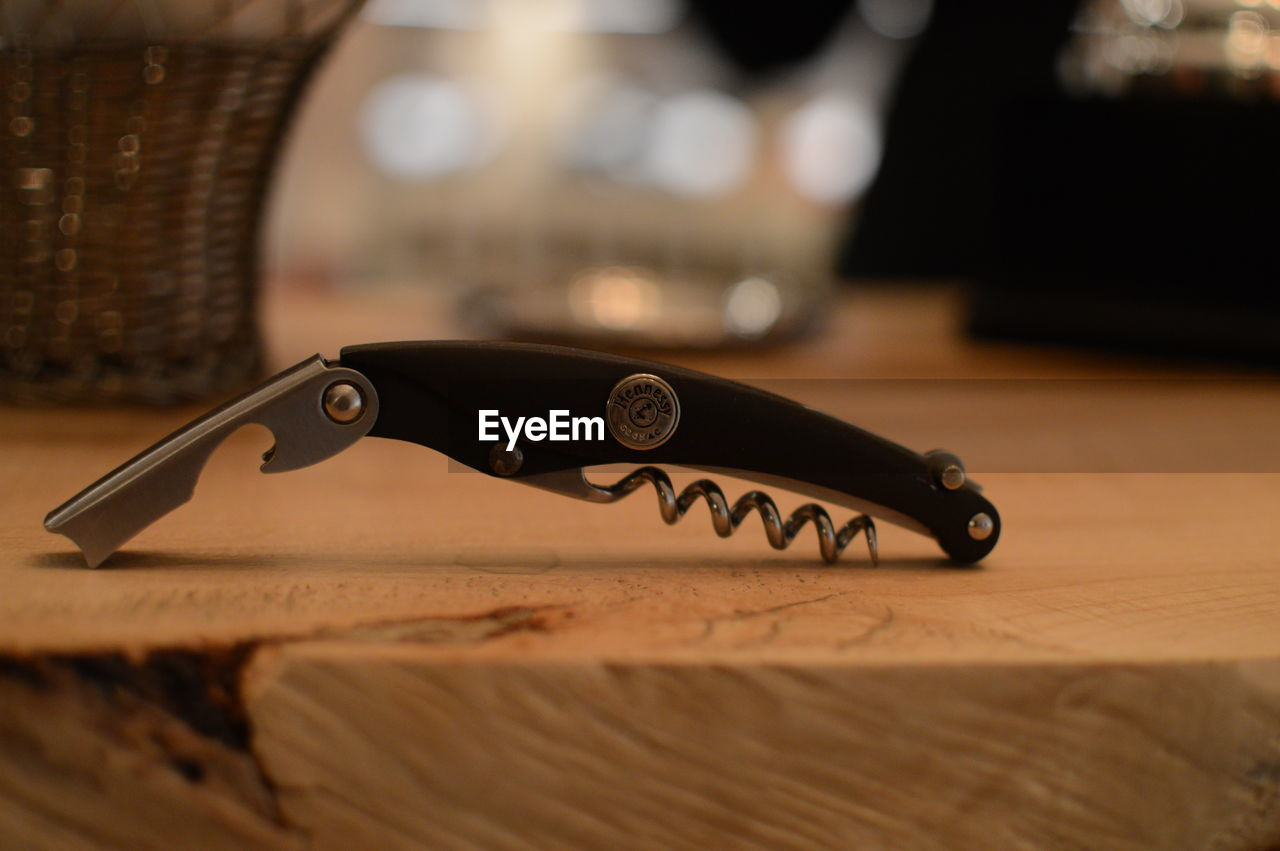 Close-up of corkscrew on wooden table