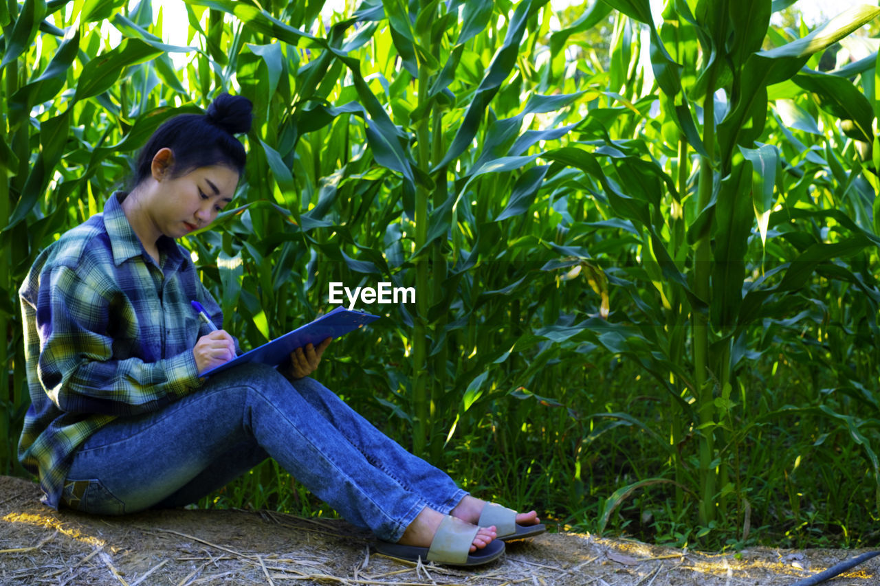 Woman writing in paper while sitting by crops at farm