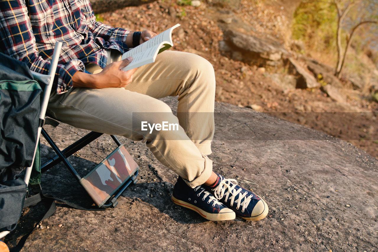 Low section of man sitting on asphalt