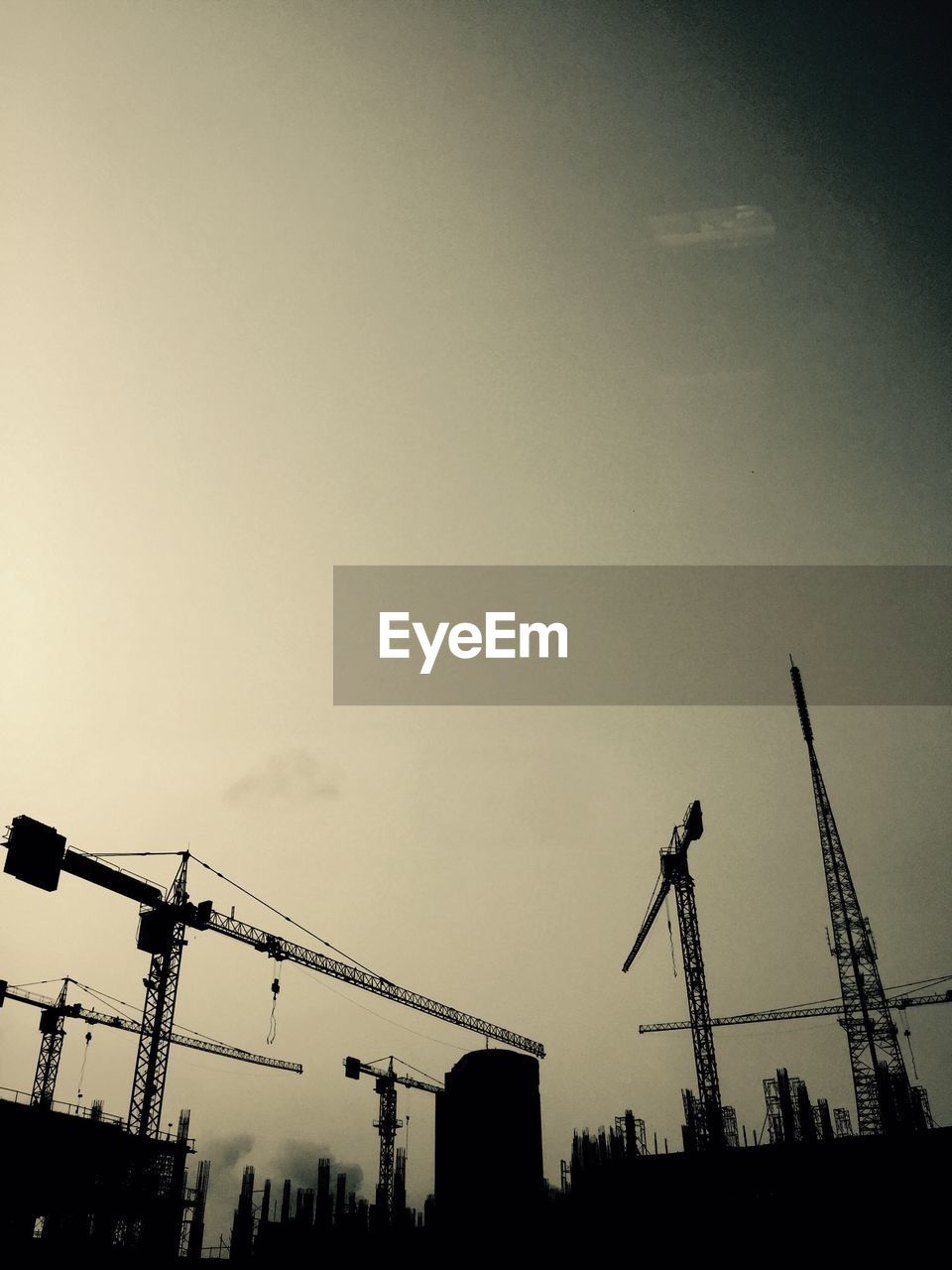 Silhouette Of Cranes At Construction Site