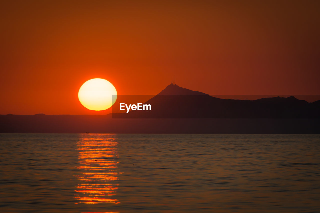 sunset, orange color, beauty in nature, scenics, sun, nature, tranquil scene, tranquility, no people, idyllic, sea, water, waterfront, outdoors, silhouette, mountain, sky, clear sky, moon