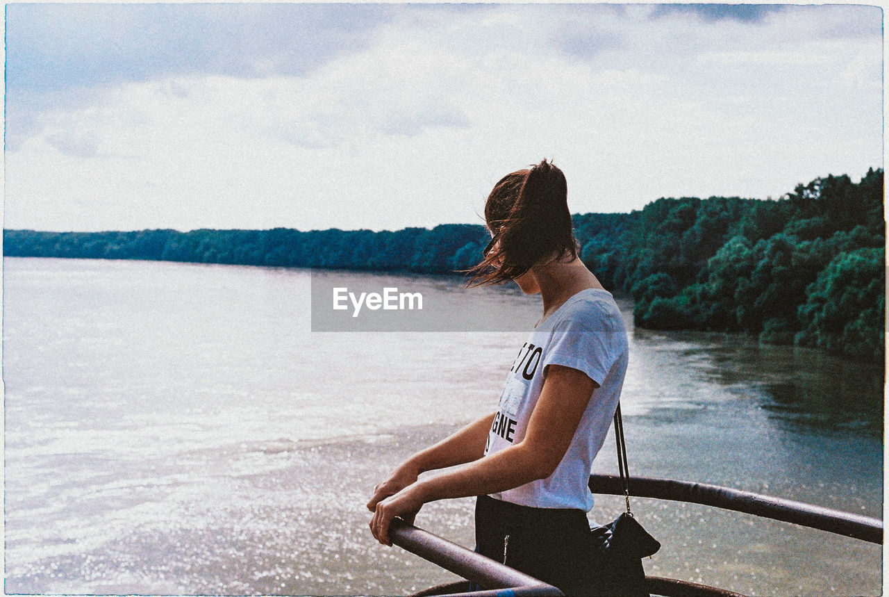 Side View Of Woman Standing By Railing While Looking At Lake Against Sky