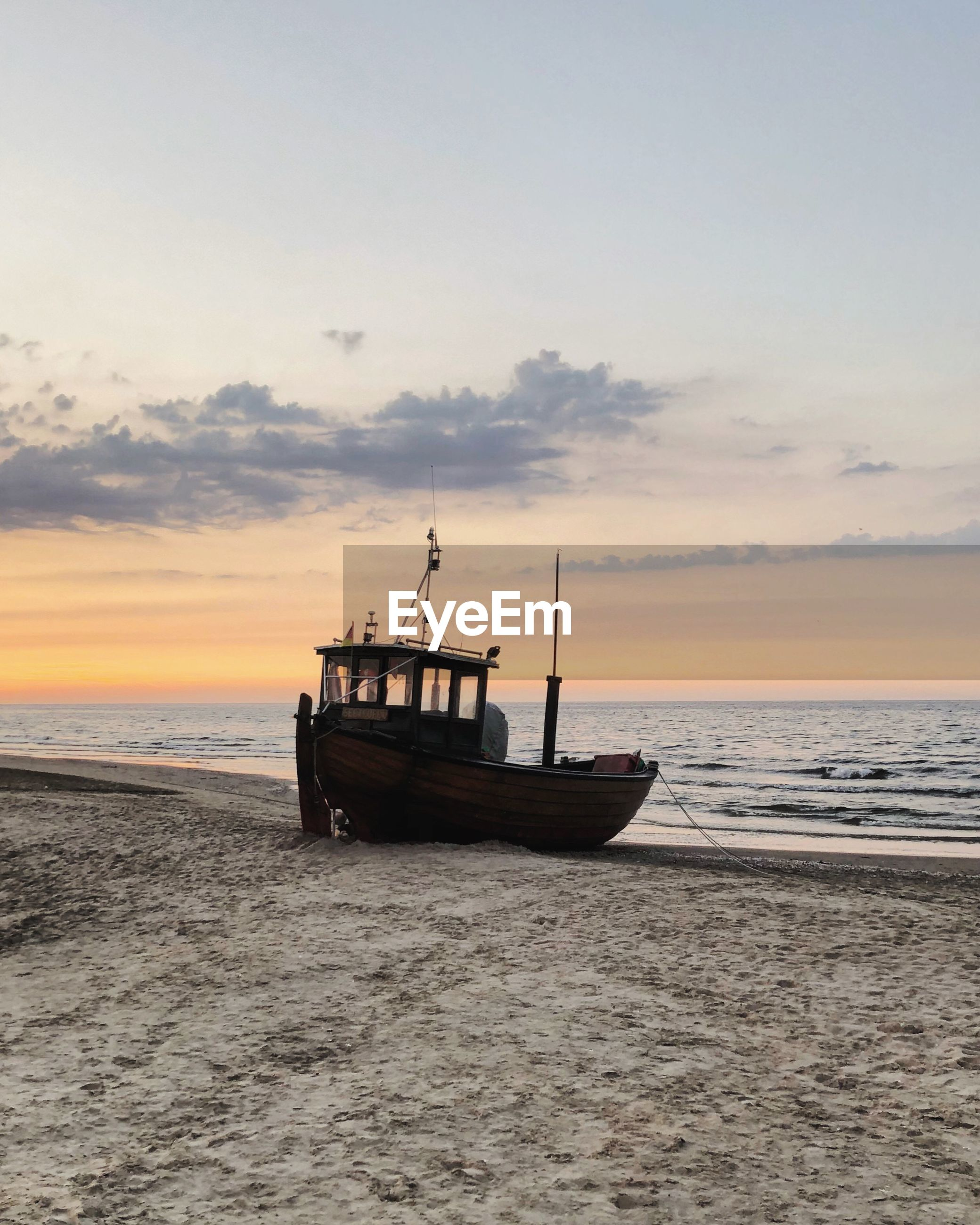 FISHING BOAT ON BEACH AGAINST SKY AT SUNSET