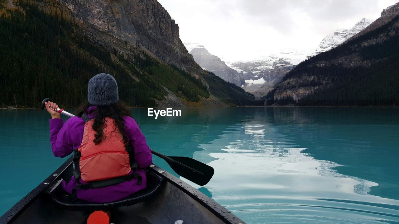 Rear View Of Woman On Boat In River