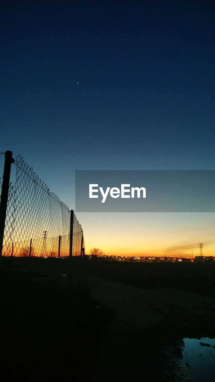 sky, copy space, sunset, fence, barrier, nature, silhouette, boundary, no people, tranquility, clear sky, blue, safety, land, tranquil scene, chainlink fence, security, landscape, field, outdoors