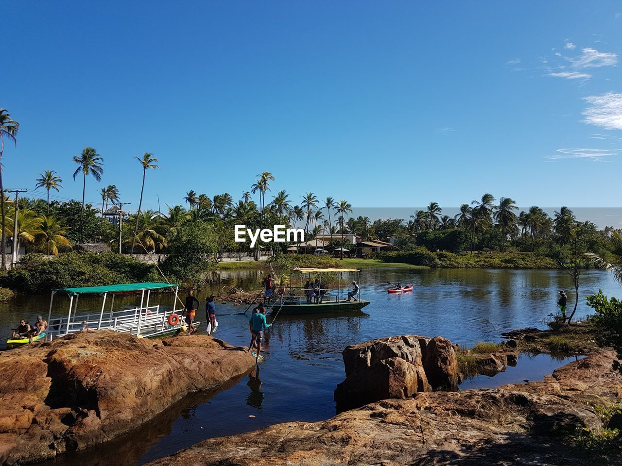water, sky, tree, plant, palm tree, nature, beauty in nature, scenics - nature, tropical climate, transportation, blue, nautical vessel, day, mode of transportation, copy space, tranquility, group of people, river, rock, outdoors