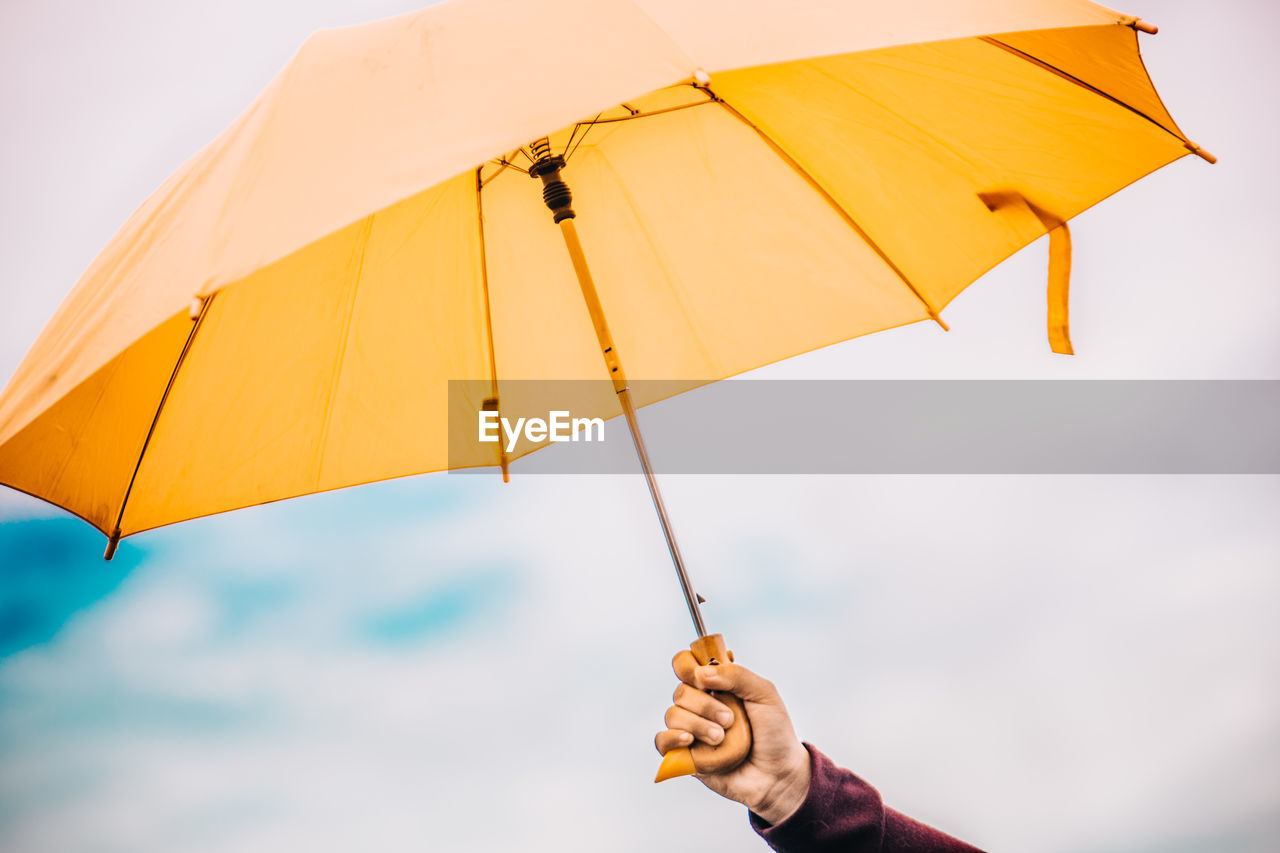 Person Holding Umbrella Against Sky