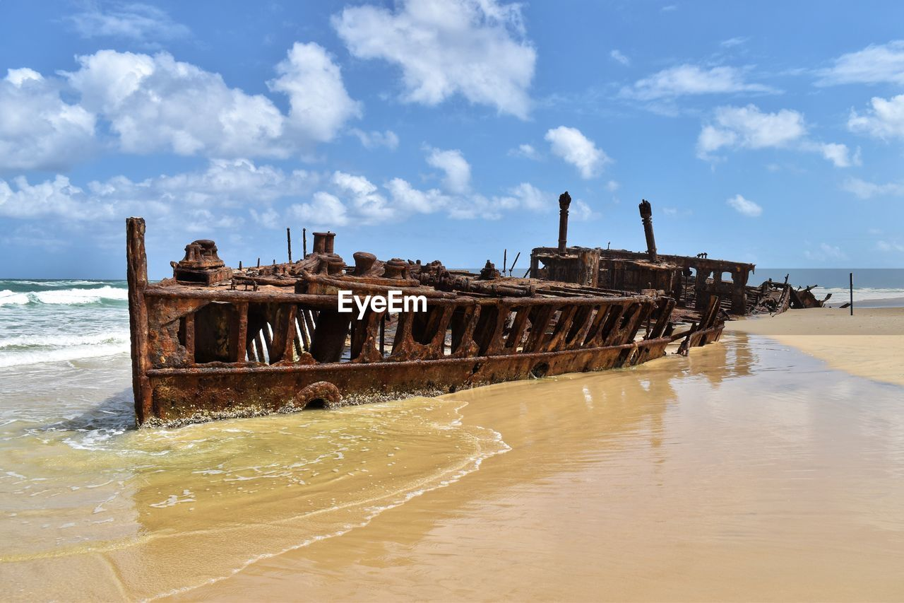 water, sea, sky, beach, shipwreck, cloud - sky, land, nature, nautical vessel, day, abandoned, decline, deterioration, obsolete, ship, damaged, transportation, run-down, mode of transportation, no people, horizon over water, outdoors