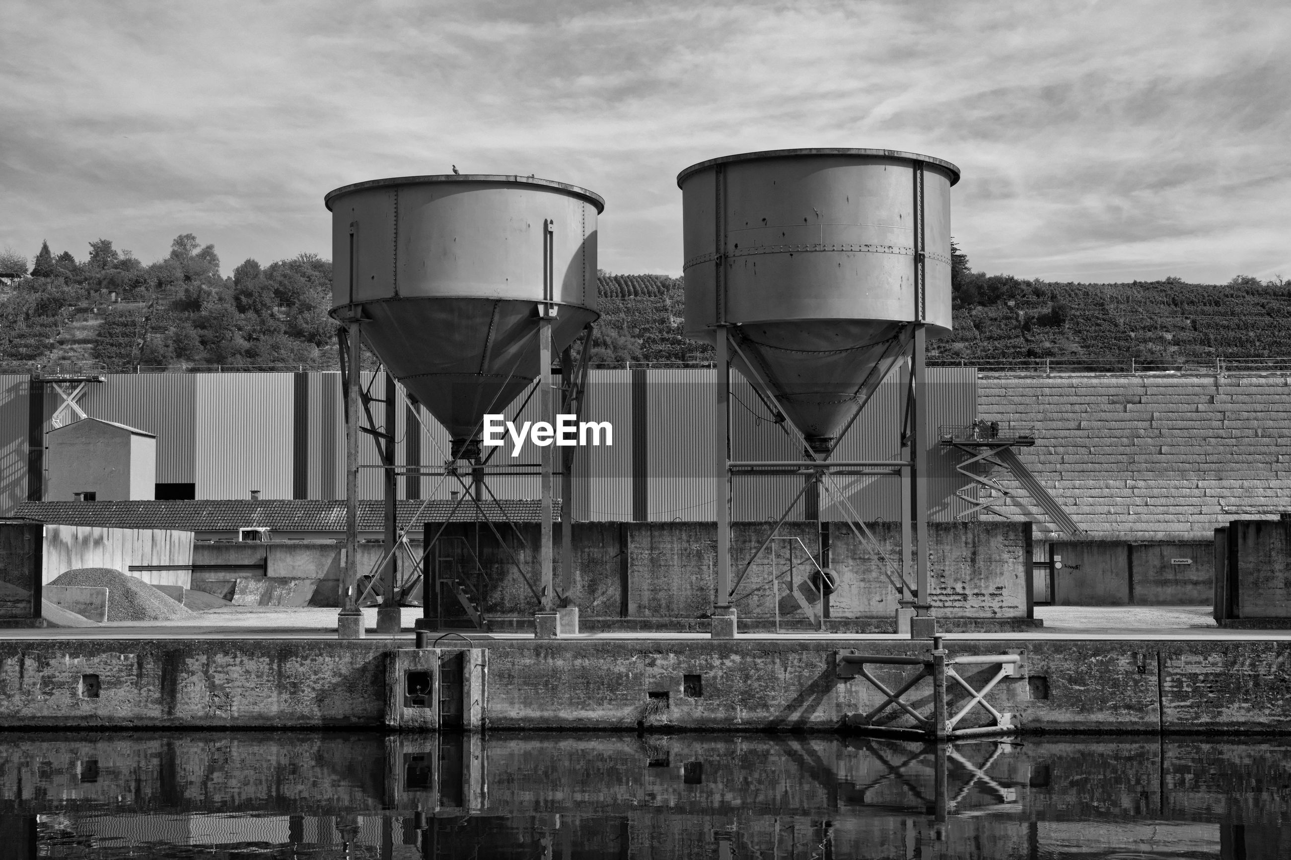 built structure, storage tank, building exterior, water tower - storage tank, architecture, sky, cloud - sky, nature, no people, day, water conservation, industry, outdoors, factory, storage compartment, metal, building, low angle view, tree, plant