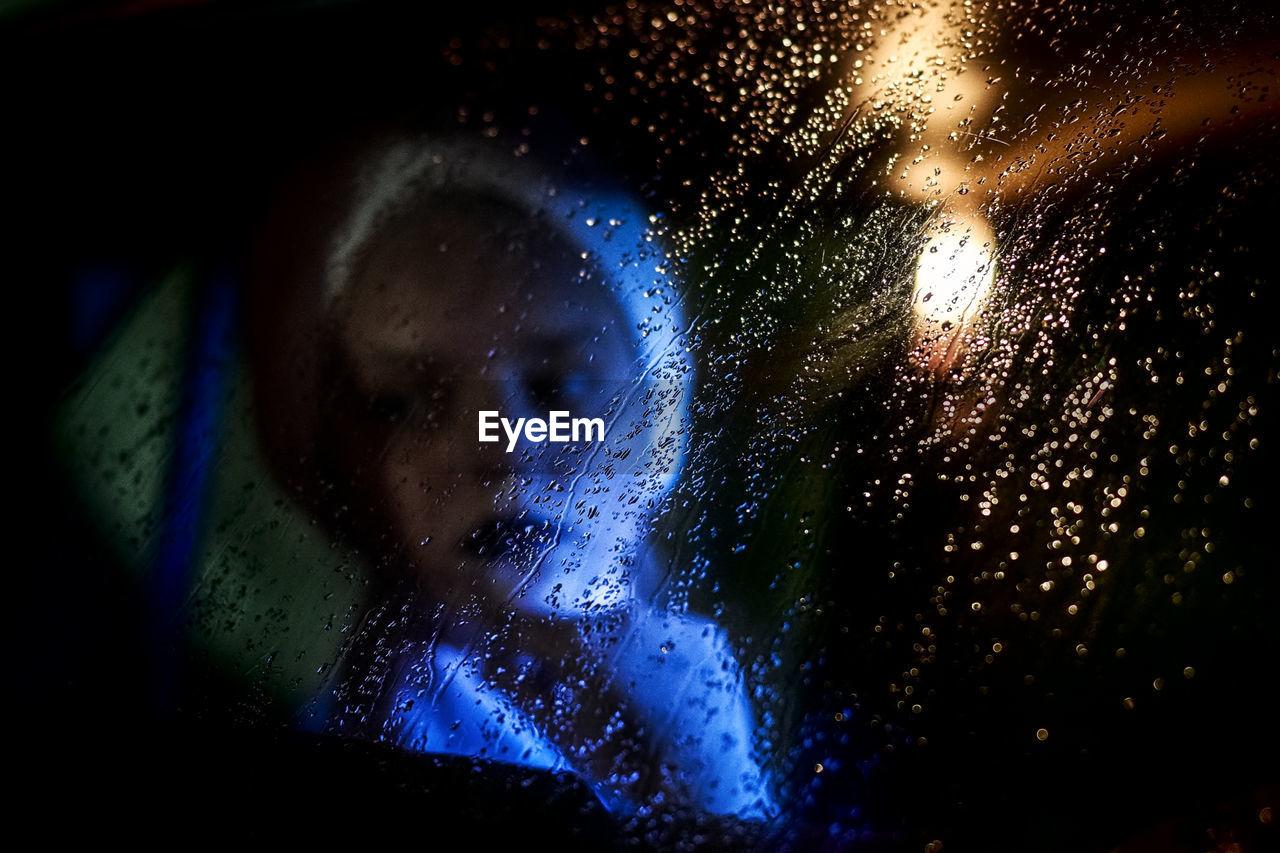 Girl Sitting In Car Seen Through Wet Glass