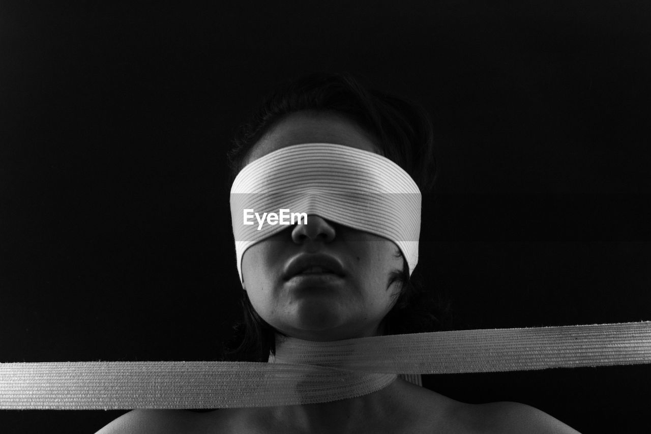 Close-Up Of Young Woman Eyes Covered With Bandage Against Black Background