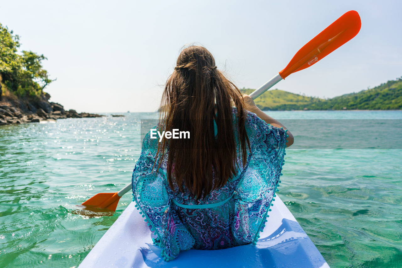Woman Kayaking On Sea Against Sky