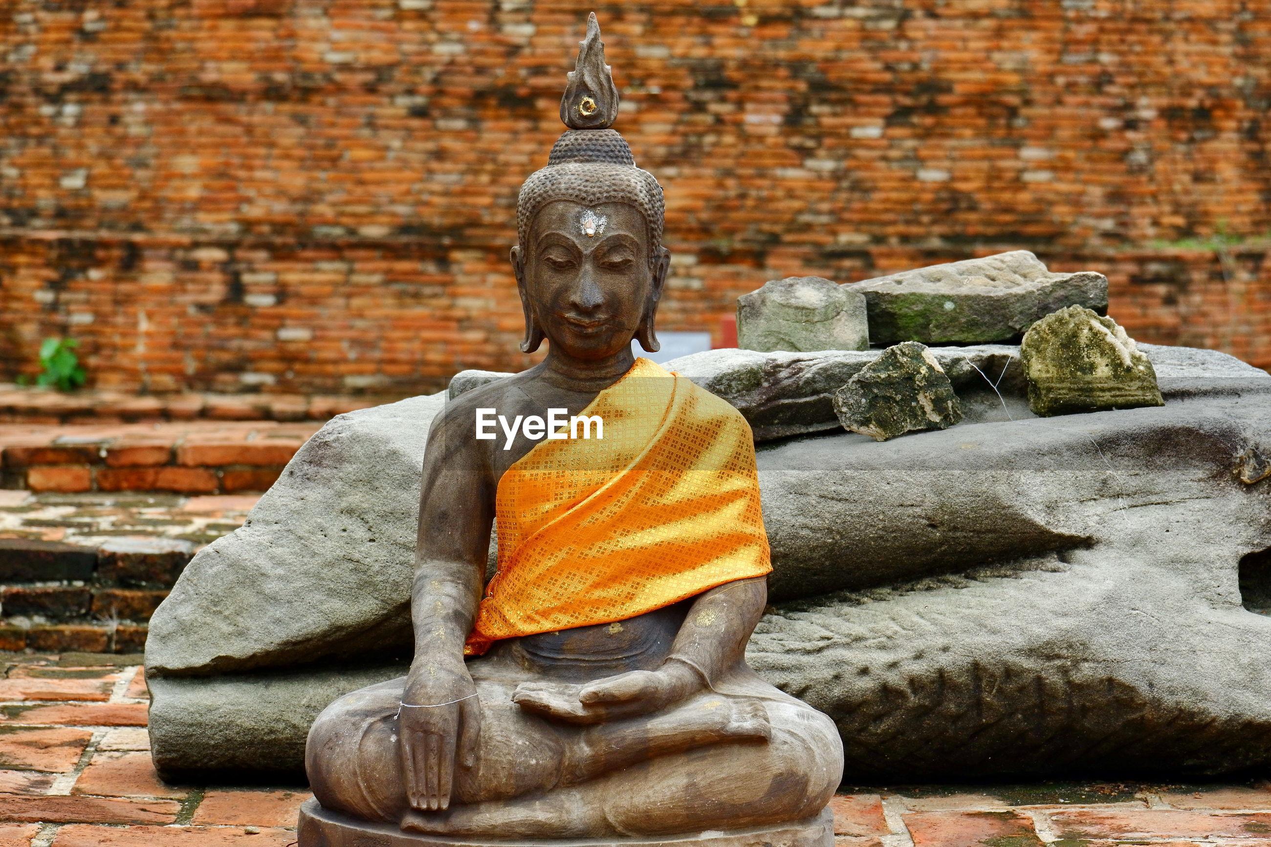 BUDDHA STATUE AGAINST WALL