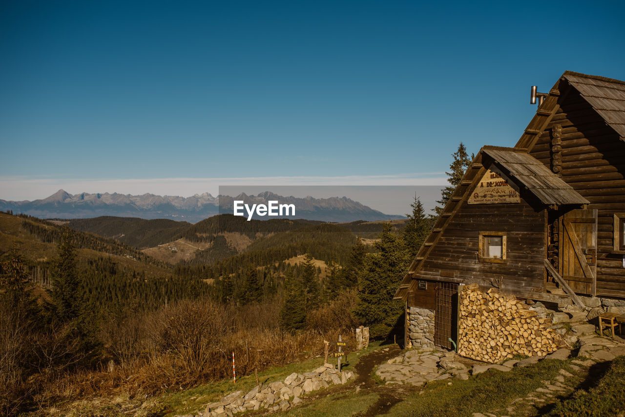 SCENIC VIEW OF MOUNTAINS AND HOUSES AGAINST CLEAR BLUE SKY